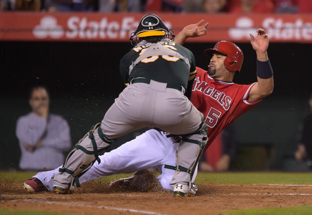 Los Angeles Angels' Albert Pujols, right, is tagged out by Oakland Athletics catcher Derek Norris while trying to score on a single by Josh Hamilton during the sixth inning of a baseball game, Tuesday, June 10, 2014, in Anaheim, Calif. (AP Photo/Mark J. Terrill)