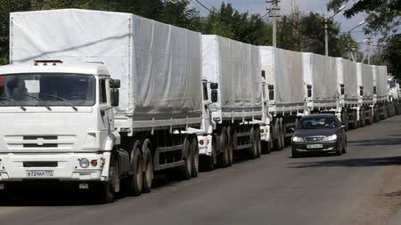 A car drives past trucks of a Russian convoy carrying humanitarian aid for Ukraine near a Russia-Ukraine border crossing point in Rostov Region