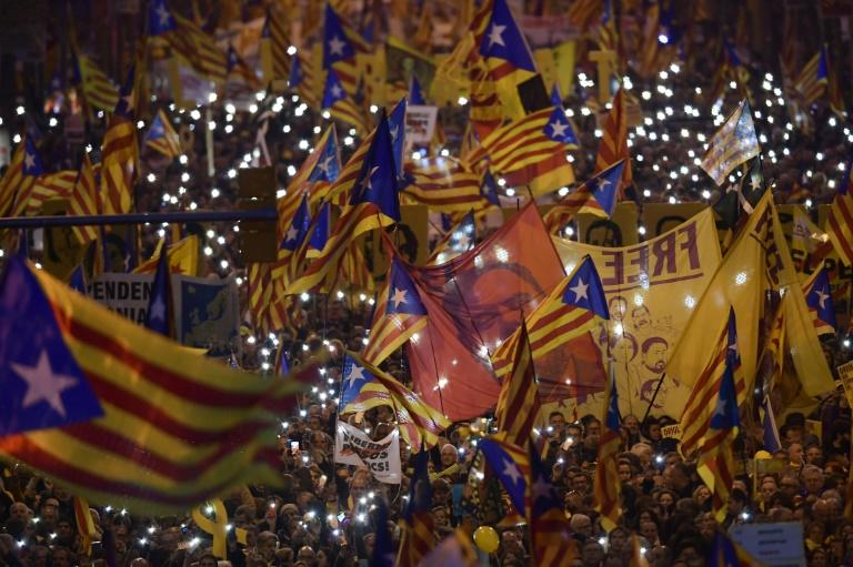 Demonstrators hold portraits of jailed Catalan separatist Oriol Junqueras and wave Catalan pro-independence Estelada flags during a protest against the trial of former Catalan separatist leaders in Barcelona