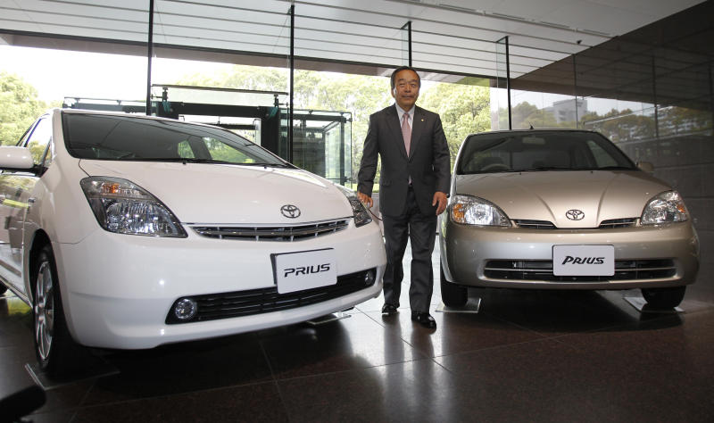 Takeshi Uchiyamada, vice chairman of Toyota Motor Corp., poses for a photo with first, seen at right, and second model of Prius at its headquarters in Tokyo, Wednesday, April 17, 2013. Toyota's global sales of gasoline-electric hybrid vehicles have surpassed 5 million in a milestone for a technology that was initially greeted with skepticism. The Japanese automaker, which said Wednesday it had sold 5.125 million hybrid vehicles as of the end of March, started selling the Prius, the world's first mass produced hybrid passenger car, in 1997. (AP Photo/Shuji Kajiyama)
