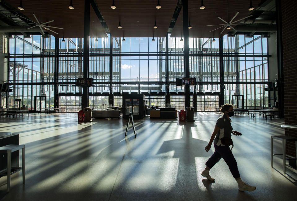 Terri Herman, an operations manager for Fox Sports Southwest, walks through the empty concourse before an opening day baseball game between the Texas Rangers and the Colorado Rockies, Friday, July 24, 2020, in Arlington, Texas. (AP Photo/Jeffrey McWhorter)