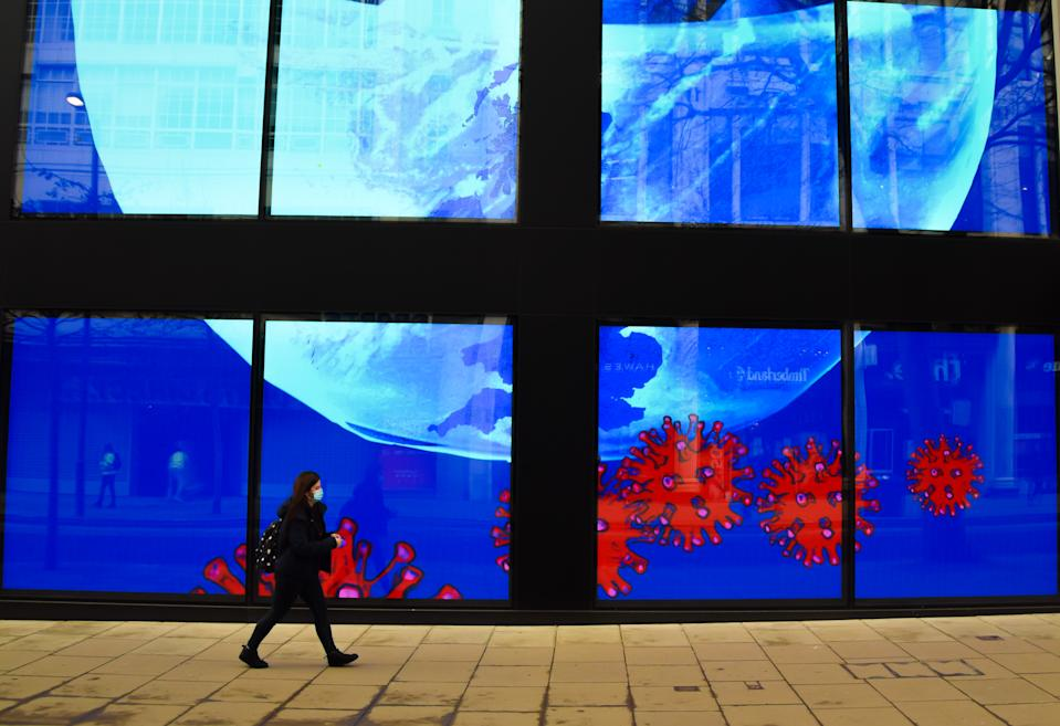 <p>A woman wearing a face mask walks past the screens displaying coronavirus art at the Flannels store on Oxford Street in London. The screens at the store are currently showing a series of artworks as part of the '#LightItBlue' campaign in support of the NHS. (Photo by Vuk Valcic / SOPA Images/Sipa USA)</p>