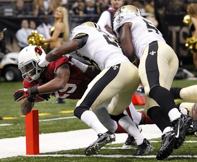 Arizona Cardinals running back Alfonso Smith (29) dives over the goal line to score a touchdown as New Orleans Saints cornerback Keenan Lewis (28) and outside linebacker David Hawthorne (57) defend in the first half of an NFL football game in New Orleans, Sunday, Sept. 22, 2013. (AP Photo/Gerald Herbert)