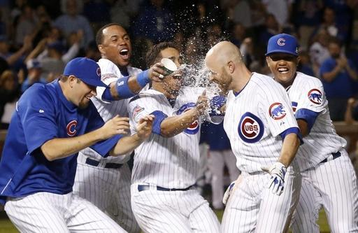 The Chicago Cubs splash Nate Schierholtz, second from right, with water, after his walk-off single ssored Anthony Rizzo, off New York Mets relief pitcher Scott Rice during the ninth inning of a baseball game Tuesday, June 3, 2014, in Chicago. The Cubs won 2-1. (AP Photo/Charles Rex Arbogast)