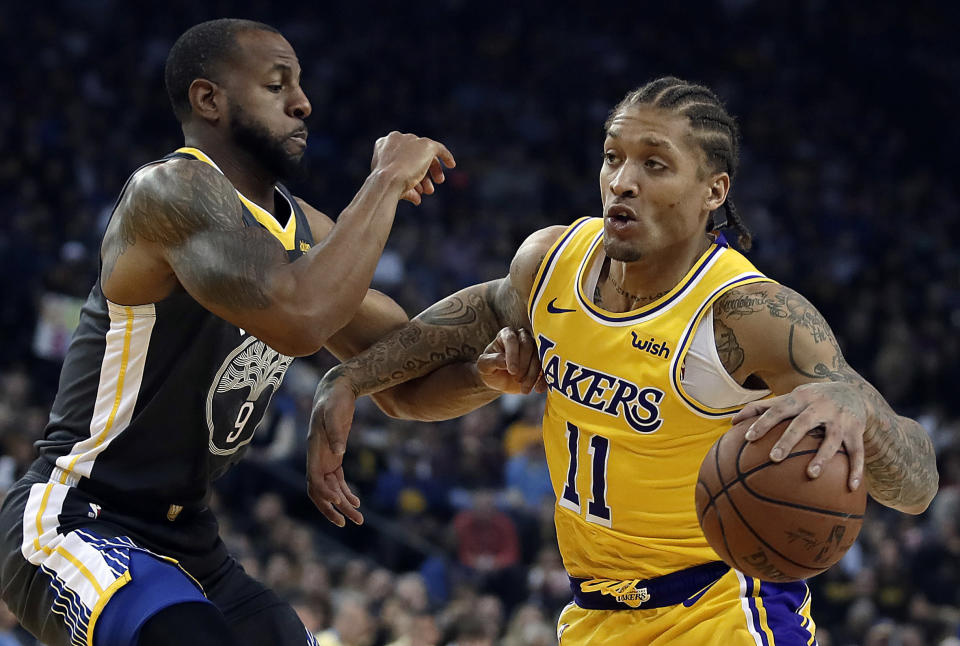 The Lakers' Michael Beasley, right, drives against the Warriors' Andre Iguodala on Saturday night. (AP)