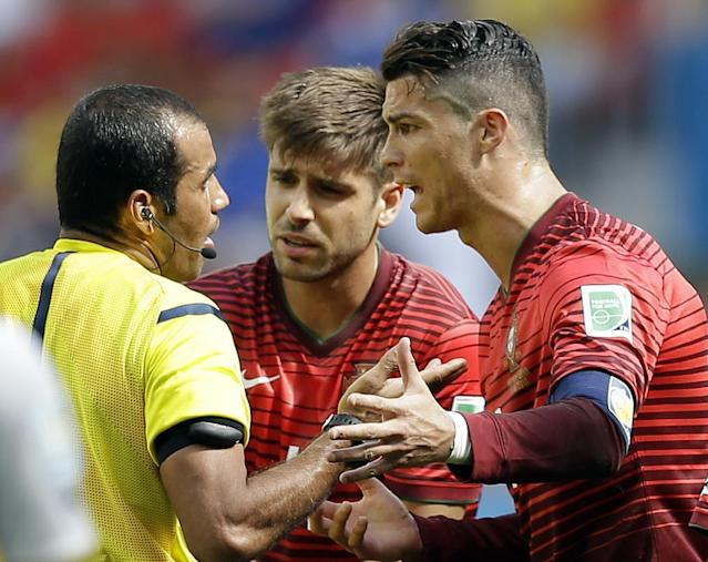 Portugal's Cristiano Ronaldo, right, and Miguel Veloso crowd around referee Nawaf Shukrallah of Bahrain during the group G World Cup soccer match between Portugal and Ghana at the Estadio Nacional in Brasilia, Brazil, Thursday, June 26, 2014. (AP Photo/Martin Mejia)