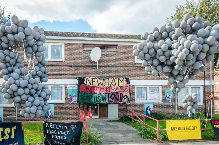Balloons and hand-drawn posters outside a low-rise council block in London
