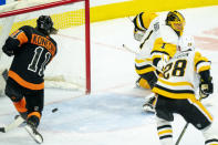 Philadelphia Flyers' Travis Konecny, left, shoots the puck past Pittsburgh Penguins' Casey DeSmith, right, for his third goal during the third period of an NHL hockey game, Friday, Jan. 15, 2021, in Philadelphia. (AP Photo/Chris Szagola)