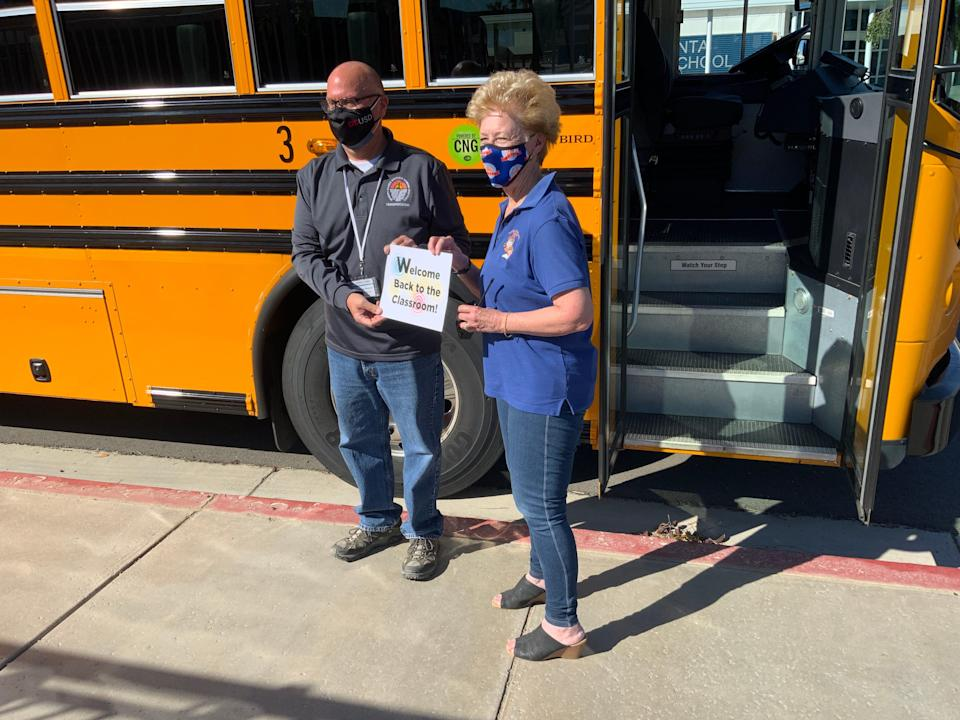 Bus driver Kevin Kreisler and Principal Carol Bishop of Harry S. Truman Elementary School practice their WELCOME for students returning to in-person learning.