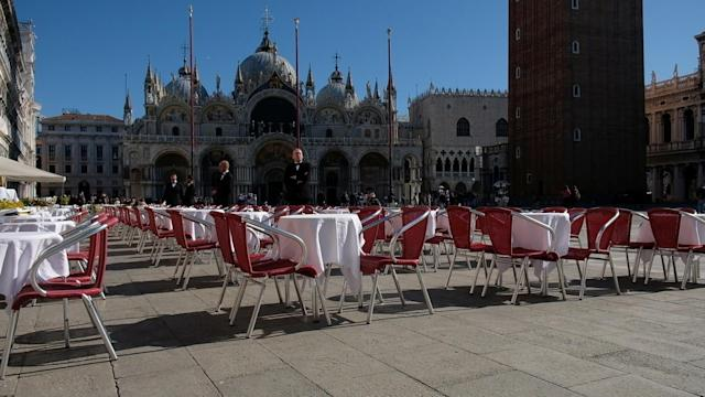 Waiters stand by an empty restaurant in St Mark's Square, Venice, which is usually full of tourists. (Reuters/Manuel Silvestri)