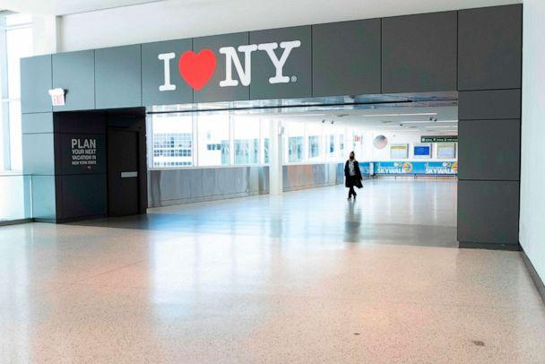PHOTO: A woman wearing a mask walks past a sing reading 'I heart NY' at Terminal 5 of John F. Kennedy Airport (JFK) amid the novel coronavirus pandemic on May 13, 2020 in Queens, N.Y. (Johannes Eisele/AFP via Getty Images)