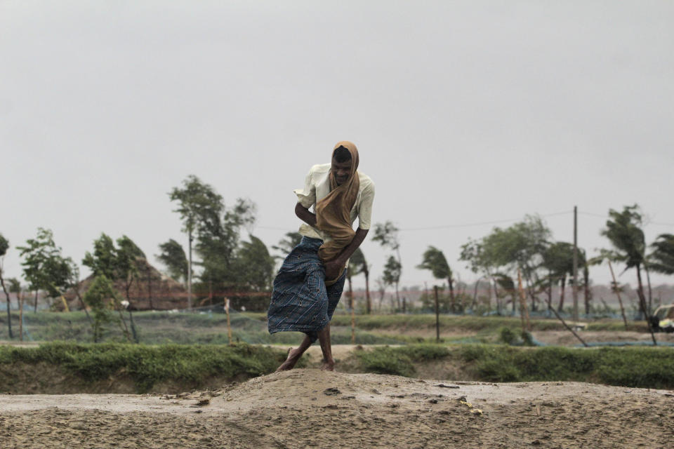 A man walks against the force of the wind ahead of Cyclone Amphan landfall, at Bhadrak district, in the eastern Indian state of Orissa, Wednesday, May 20, 2020. A strong cyclone blew heavy rains and strong winds into coastal India and Bangladesh on Wednesday after more than 2.6 million people were moved to shelters in a frantic evacuation made more challenging by coronavirus. (AP Photo)