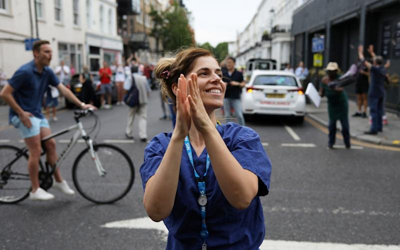 Members of the public and NHS workers react at the Chelsea and Westminster Hospital during the Clap for our Carers campaign - Kevin Coombs/Reuters