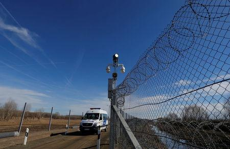 A Hungarian police van passes by an intelligent fence post as it patrols the fortified Hungary-Serbia border near the village of Asotthalom