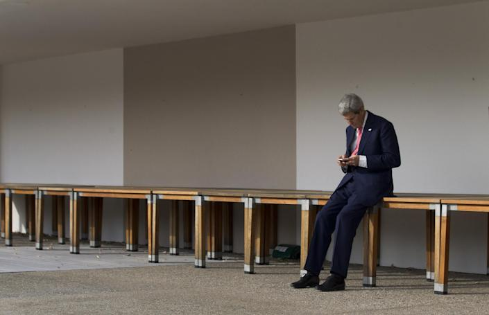 U.S. Secretary of State John Kerry checks his phone before a meeting with EU High Representative for Foreign Affairs, Catherine Ashton and Iranian Foreign Minister Mohammad Javad Zarif in Geneva, Switzerland, Saturday Nov. 9, 2013. US Secretary of State John Kerry and his counterparts from Britain, France and Germany arrived in Geneva with the talks at a critical stage following a full day of negotiations Thursday and said some obstacles remained in the way of any agreement offering sanctions reductions for nuclear concessions. (AP Photo/Jason Reed, Pool)