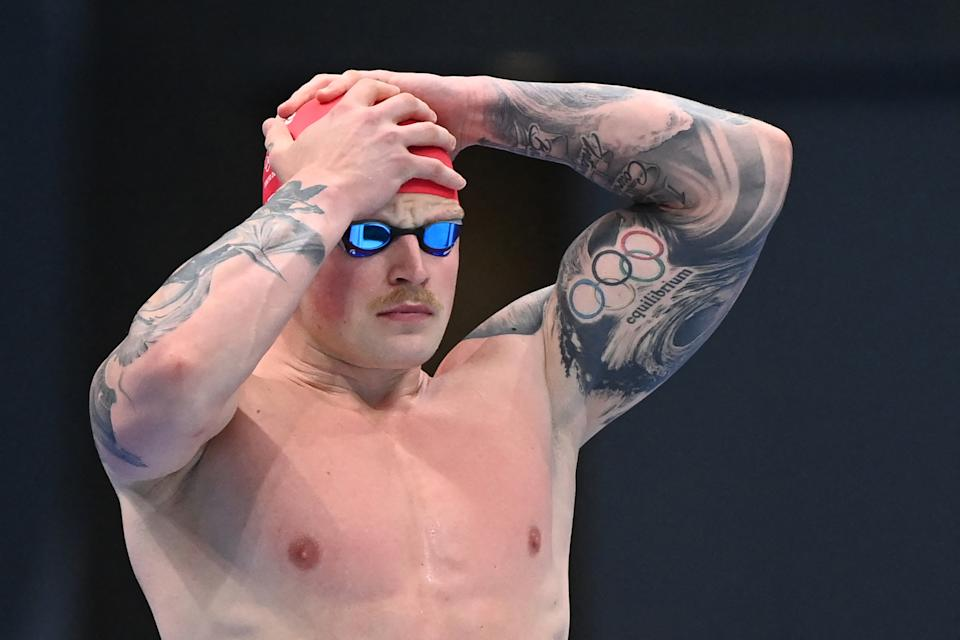 <p>Britain's Adam Peaty prepares to compete in a heat for the men's 100m breaststroke swimming event during the Tokyo 2020 Olympic Games at the Tokyo Aquatics Centre in Tokyo on July 24, 2021. (Photo by Attila KISBENEDEK / AFP) (Photo by ATTILA KISBENEDEK/AFP via Getty Images)</p>