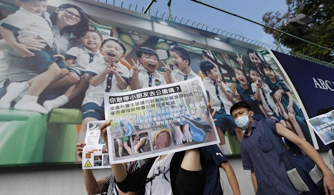 Protesters hold up posters against police use of tear gas. Photo: EPA-EFE