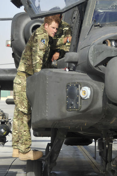 Britain's Prince Harry is shown an Apache helicopter by a member of his squadron, obscured behind, (name not provided) at Camp Bastion in Afghanistan, Friday Sept. 7, 2012. Prince Harry, known to the military as Capt. Harry Wales, will be based at Camp Bastion during his tour of duty as a co-pilot gunner on attack helicopters. (AP Photo/Cpl Paul Morrison, Army Photographer, MOD)