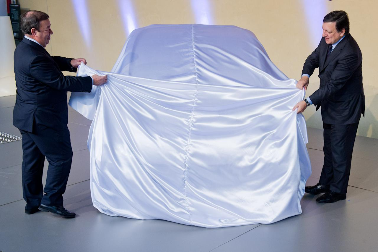 "BRUSSELS, BELGIUM - JANUARY 24:  EU Commission President Jose Manuel Barroso (R) and Jesus Echave, chairman of the HIRIKO-AFYPAIDA corporate consortiumk, unveil the first prototype of the HIRIKO electric car, during the global launch of Hiriko Driving Mobility, at the EU Commssion headquarters on January 24, 2012 in Brussels, Belgium. The electronic eco-friendly vehicle will be manufactured in deprived areas of cities who take up Hiriko's ""social purpose"" model. Malmo in Sweden has already signed up to trial Hiriko with Berlin, Barcelona, Vitoria-Gasteiz (the second largest Basque city), San Francisco, and Hong Kong expected to follow suit.  (Photo by Geert Vanden Wijngaert/Getty Images)"