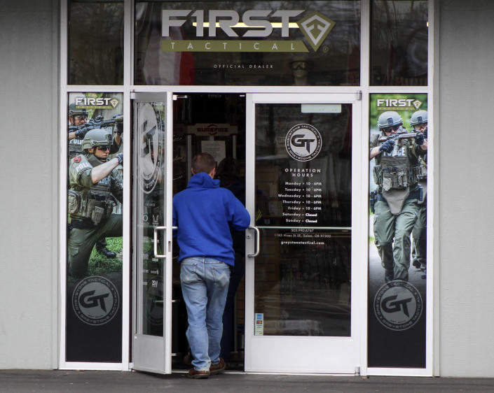 """FILE - In this Feb. 19, 2021, file photo, a man enters a gun shop in Salem, Ore. The first legal test of whether a wave of U.S. counties can legally declare themselves """"Second Amendment Sanctuaries,"""" and refuse to enforce certain gun laws is playing out in a rural Oregon logging county. The measure Columbia County voters narrowly approved last year bans local officials from enforcing most federal and state gun laws, which includes things like universal background checks or any prohibition on carrying guns. (AP Photo/Andrew Selsky, File)"""