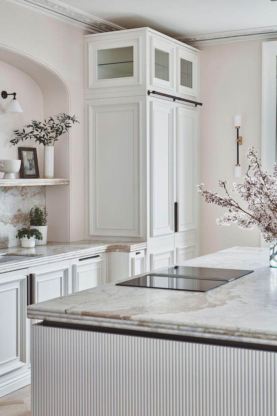 """<p>This kitchen uses plenty of surface detailing – ridged fronts to the kitchen island, decorative moulding, and reeded glass – to add interest and depth to pure white cabinetry. A clever device to prevent your white cabinets from appearing too slick or clinical.</p><p>Pictured: <a href=""""https://www.blakeslondon.com/bathtownhouse"""" rel=""""nofollow noopener"""" target=""""_blank"""" data-ylk=""""slk:Kitchen by Blakes London"""" class=""""link rapid-noclick-resp"""">Kitchen by Blakes London</a></p>"""