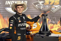 Pato O'Ward poses with the trophy as he celebrates his victory at an IndyCar Series auto race at Texas Motor Speedway on Sunday, May 2, 2021, in Fort Worth, Texas. (AP Photo/Richard W. Rodriguez)