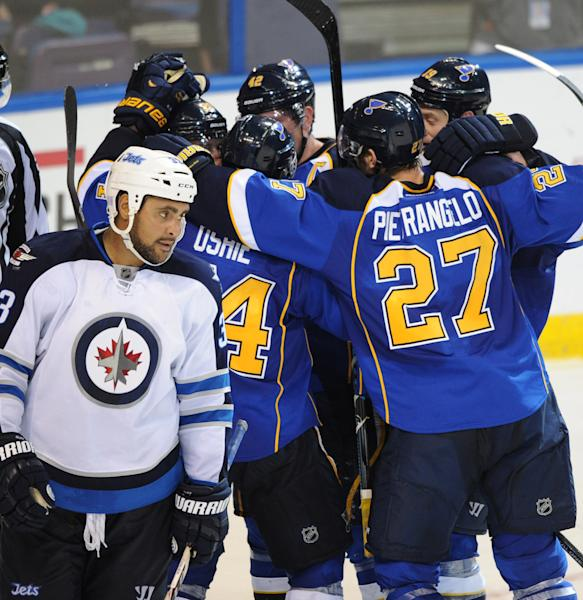 St. Louis Blues' Alex Pietrangelo (27), T.J. Oshie, David Backes (42) and Jay Bouwmeester (19) surround teammate Alexander Steen after his goal as Winnipeg Jets' Dustin Byfuglien, left, skates away during the third period of an NHL hockey game Tuesday, Oct. 29, 2013, in St. Louis. The Blues won 3-2. (AP Photo/Bill Boyce)