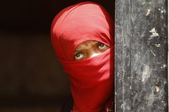 A woman from the Akhdam community looks from behind the door of her hut in a slum area in Sanaa March 4, 2012.
