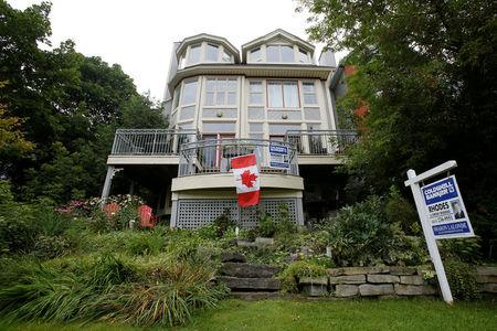 FILE PHOTO: A Canadian flag hangs from the deck of a house for sale in Ottawa