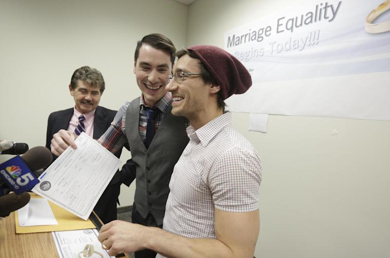 CORRECTS SPELLING TO WILK IN SECOND REFERENCE INSTEAD OF WILL - Charlie Gurion, center, and David Wilk hold up their marriage license as Cook County Clerk David Orr, left looks on Friday, Feb. 21, 2014, in Chicago. Same-sex couples in Illinois' largest county began receiving marriage licenses immediately after a federal judge's ruling Friday that some attorneys said could give county clerks statewide justification to also issue the documents right away. Illinois approved same-sex marriage last year; the new law takes effect June 1. However, U.S. District Judge Sharon Johnson Coleman ruled Friday that same-sex marriages can begin now in Cook County, where Chicago is located. Gurion and Wilk were the first couple to show up to get a license after the judge made her ruling. (AP Photo/M. Spencer Green)