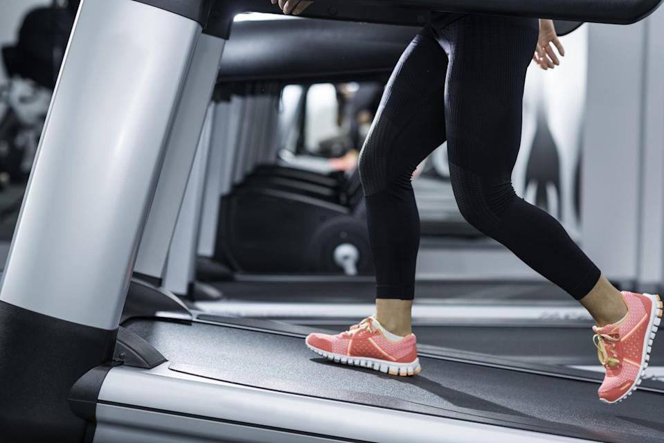 Woman using incline threadmill in modern gym. Incline threadmills are used to simulate uphill walking or running and deliver additional workout benefits to users. Woman is wearing black yoga pants andrunning sports shoes.