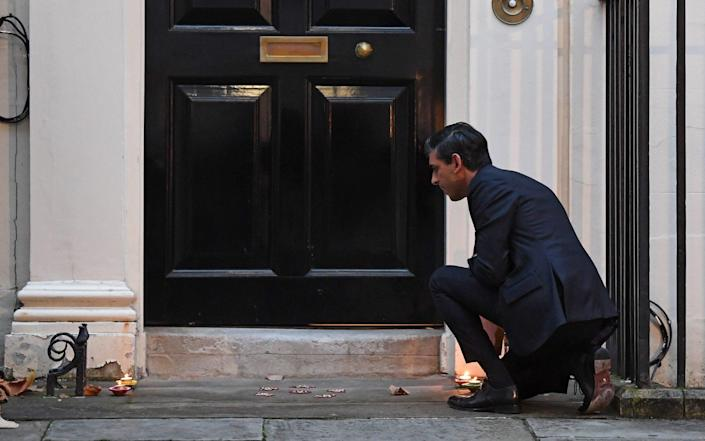 Mr Sunak lights candles outside Number 11 Downing Street ahead of Diwali celebrations - Stefan Rousseau/PA