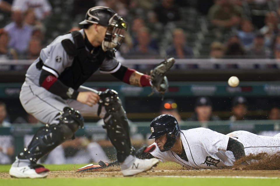 Detroit Tigers' Victor Reyes slides safely into home plate as Chicago White Sox catcher Yasmani Grandal (24) receives the throw in the third inning of a baseball game in Detroit, Monday, Sept. 20, 2021. (AP Photo/Paul Sancya)