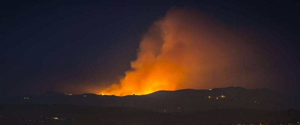 Wildfire burning in the Northern Nevada Hills at night with glow and smoke