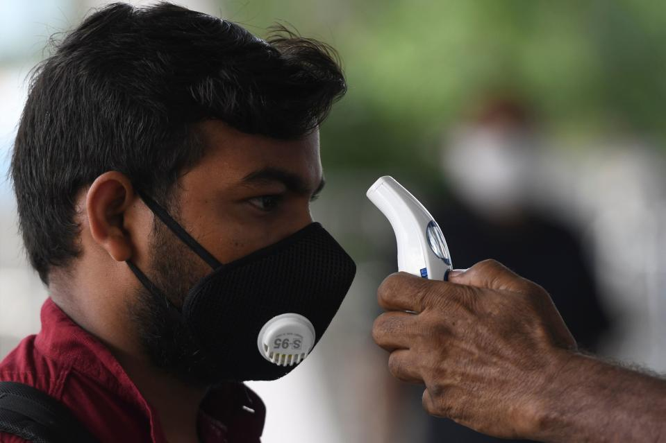 An airport staff checks the temperature of a passenger at the Kamaraj domestic airport during the first day of resuming of domestic flights after the government imposed a nationwide lockdown as a preventive measure against the spread of the COVID-19 coronavirus, in Chennai on May 25, 2020. - Confusion and concern reigned at Indian airports on May 25 as domestic flights tentatively resumed after two months, even as coronavirus cases continued to surge at record rates. (Photo by Arun SANKAR / AFP) (Photo by ARUN SANKAR/AFP via Getty Images)