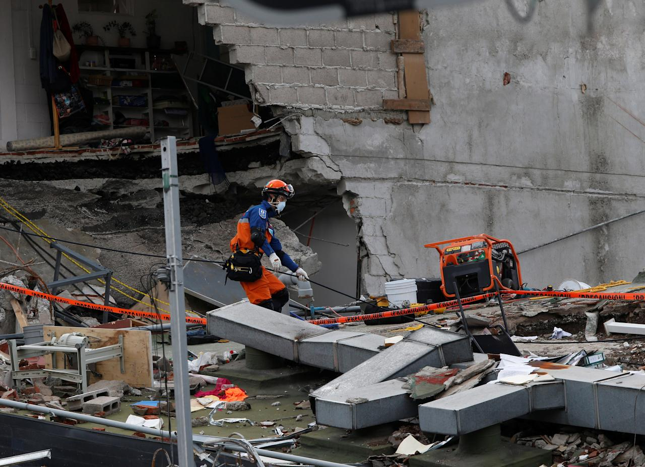 A member from Japan rescue team searches for survivors in the rubble of a collapsed building after an earthquake in Mexico City, Mexico September 22, 2017. REUTERS/Henry Romero