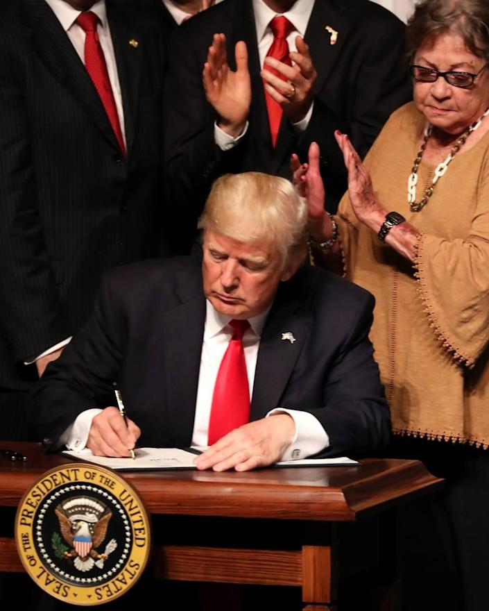 MIAMI, FL - JUNE 16: U.S. President Donald Trump signs policy changes he is making toward Cuba at the Manuel Artime Theater in the Little Havana neighborhood on June 16, 2017 in Miami, Florida. The President will re-institute some of the restrictions on travel to Cuba and U.S. business dealings with entities tied to the Cuban military and intelligence services. (Photo by Joe Raedle/Getty Images)
