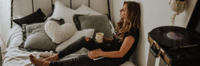 Woman sitting on her bed with cup of coffee