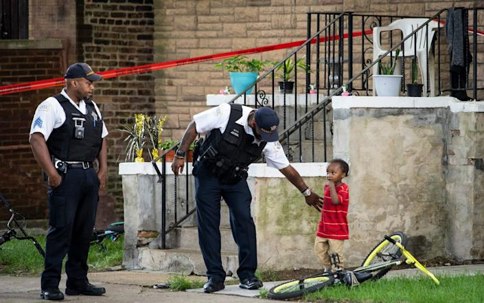 A Chicago police officer helps a child walk through an area being investigated after two men were shot on Friday, July 3 - Ashlee Rezin Garcia/Chicago Sun-Times
