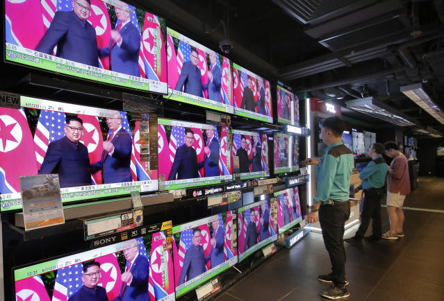 <p>A man watches TV screens showing U.S. President Donald Trump, right, meeting with North Korean leader Kim Jong Un in Singapore, during a news program In Hong Kong, Tuesday, June 12, 2018. (AP Photo/Vincent Yu) </p>