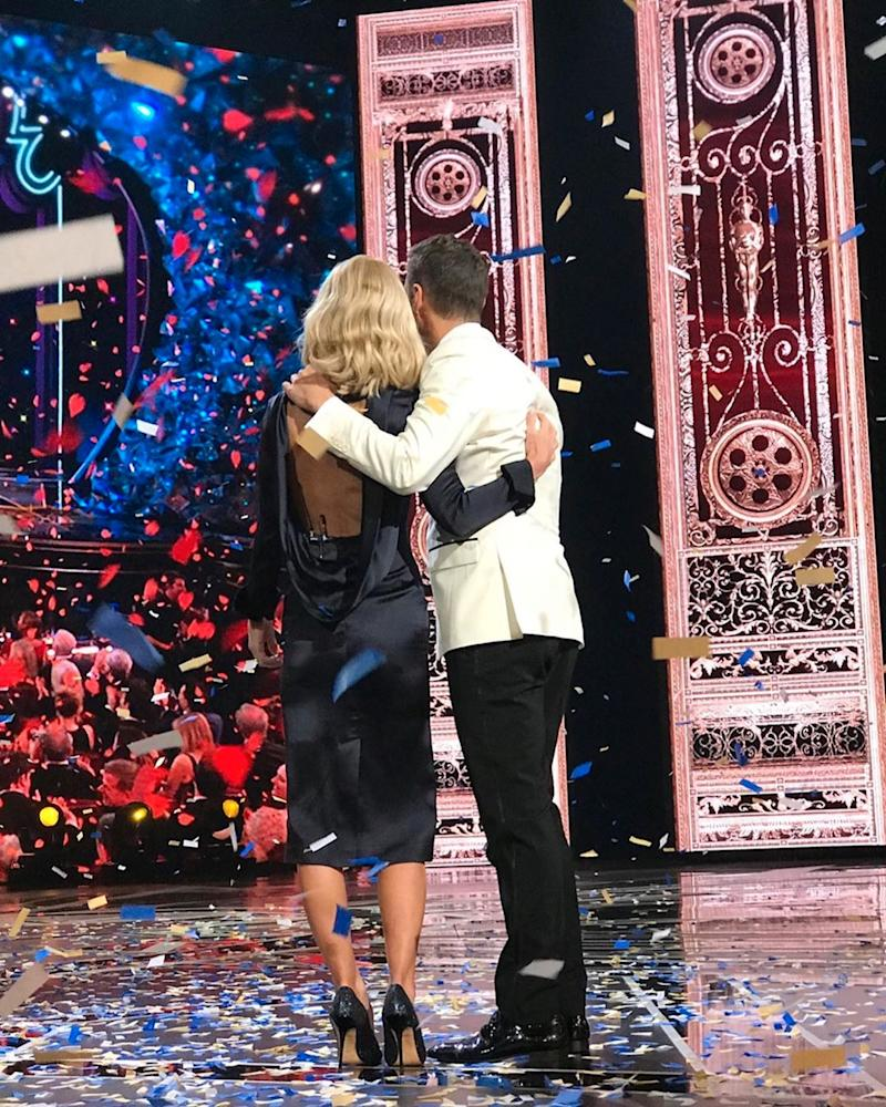 Kelly Ripa and Ryan Seacrest shot from behind on stage