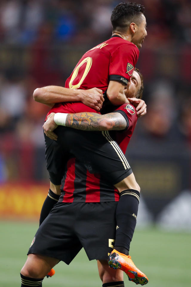 Atlanta United midfielder Miguel Almiron (10) reacts with teammate Leandro Gonzalez (5) after scoring in the second half of an MLS soccer game against the D.C. United on Sunday, March 11, 2018, in Atlanta. The Atlanta United won the game 3-1. (AP Photo/Todd Kirkland)