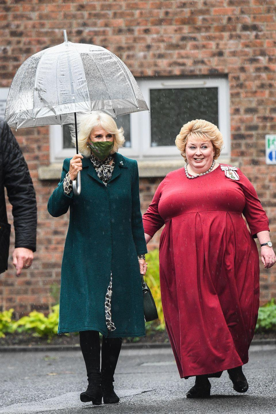 <p>Heading to her next engagement, the Duchess of Cornwall wore a green mask, matching her coat, and toted a clear umbrella. </p>