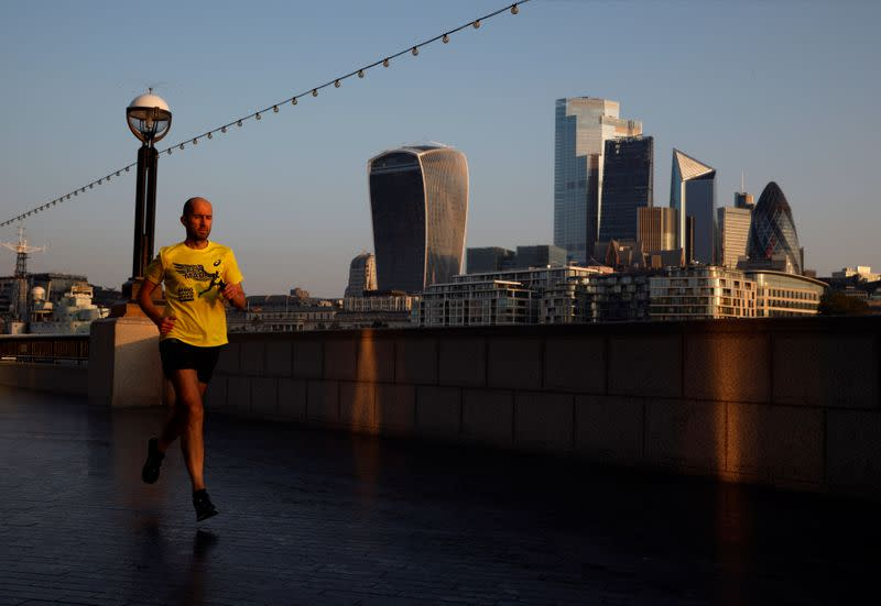 A man runs at sunrise, with the City of London financial district in the background