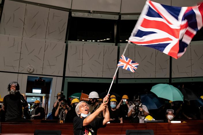 A protester waves the British Union Jack flag in the parliament chamber after they broke into the government headquarters in Hong Kong on July 1, 2019. (Photo: Philip Fong/AFP/Getty Images)