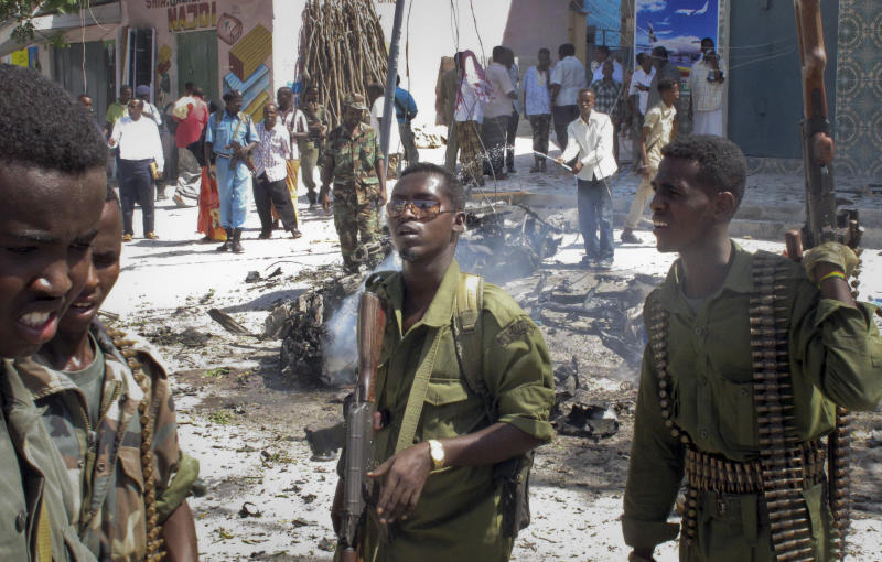 Somali government soldiers secure the area around the wreckage of a suicide car bombing that appeared to be targeting a convoy of African Union and Somali troops in Mogadishu, Somalia Friday, Dec. 14, 2012. A Somali police official says a suicide car bomb explosion in Mogadishu killed only the bomber but wounded three bystanders when the car exploded. (AP Photo/Mohamed Sheikh Nor)