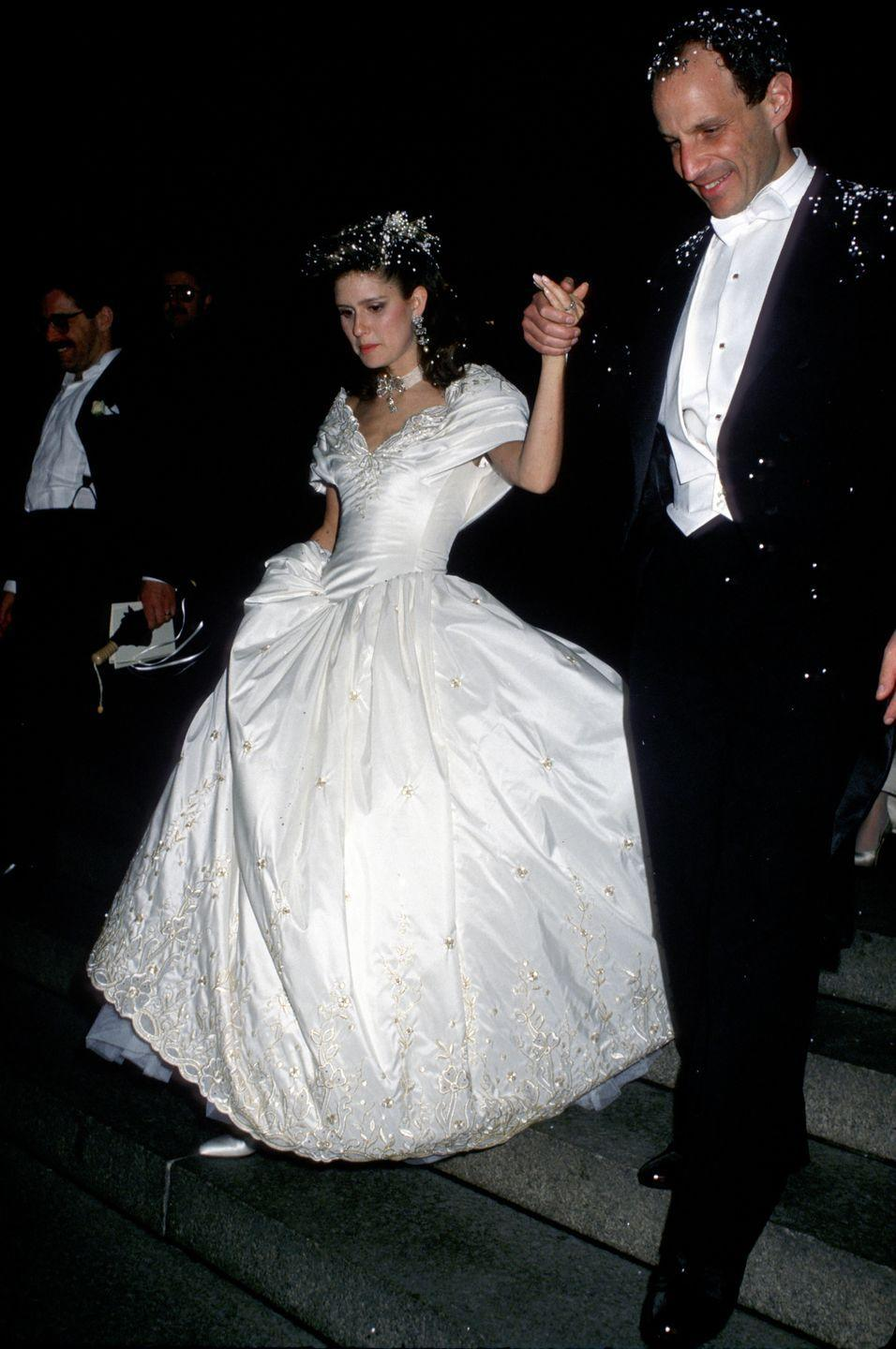 """<p>Jonathan Tisch and Laura Steinberg married in 1988 at the Central Synagogue in NYC. Their wedding made the pages of <a href=""""https://www.nytimes.com/1987/05/03/style/jonathan-tisch-executive-to-marry-laura-steinberg.html"""" rel=""""nofollow noopener"""" target=""""_blank"""" data-ylk=""""slk:The New York Times"""" class=""""link rapid-noclick-resp""""><em>The New York Times</em></a>, obviously, though the couple later divorced. Jonathan's wealth can be traced back to his family's empire of hotels, which now all fall under the Loews Corporation. The American conglomerate has diversified its portfolio to include insurance, oil drilling, and pipeline transport. </p><p>Laura wore an <a href=""""https://www.nytimes.com/1988/04/19/nyregion/candlelight-wedding-joins-2-billionaire-families.html"""" rel=""""nofollow noopener"""" target=""""_blank"""" data-ylk=""""slk:off-white taffeta dress"""" class=""""link rapid-noclick-resp"""">off-white taffeta dress</a> that was delicately embroidered in gold and had a seven-foot train. Her tulle veil was held in place by a diamond and pearl tiara. Meanwhile, her matron of honor and bridesmaids all wore dresses by Arnold Scaasi. As reported by <em>The New York Times,</em> """"The families declined a request by <em>Life </em>magazine to document what was being called the wedding of the 80s."""" More than 500 guests attended the wedding, including the likes of Barbara Walters and Helen Gurley Brown. </p>"""