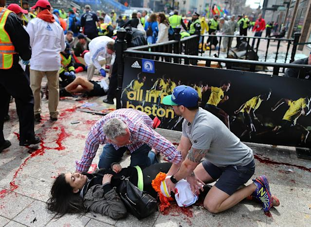 ADDS NAME OF VICTIM - FILE - In this April 15, 2013 file photo, Sydney Corcoran, of Lowell, Mass. is tended to at the finish line of the Boston Marathon after two bombs exploded, in Boston. As people lay badly bleeding in the smoke of the Boston Marathon bombings, rescuers immediately turned to a millennia-old medical device to save their lives _ the tourniquet. Using belts, shirts and other materials, they tied off bleeding limbs in fast-acting bids to prevent major blood loss, shock and death. Such fast work no doubt saved many lives, doctors at Boston area hospitals said. (AP Photo/The Boston Globe, John Tlumacki) MANDATORY CREDIT, BOSTON HERALD OUT, QUINCY OUT, MAGS OUT, NO SALES.