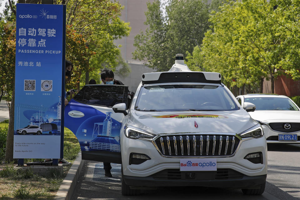 A man wearing a face mask gets into a Baidu Apollo Robotaxi at a passenger pickup point setup at the Shougang Park in Beijing, Sunday, May 2, 2021. Chinese tech giant Baidu rolled out its paid driverless taxi service on Sunday, making it the first company that commercialized autonomous driving operations in China. (AP Photo/Andy Wong)