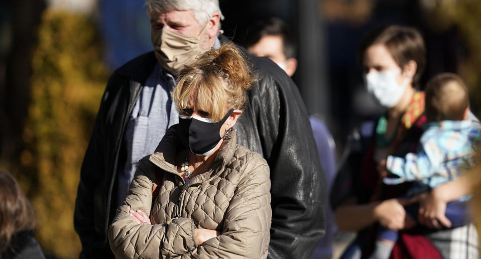 Concerned man and woman shown on the street in surgical masks.